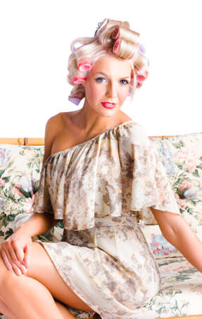 printed: Blonde Caucasian woman with curlers wearing pink and lavender curled and flower print one shoulder dress, sitting on a floral print bamboo coach