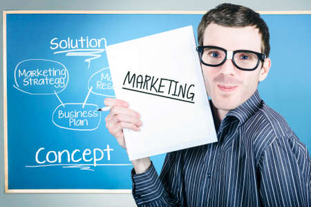 dork: Humorous portrait of an education marketing man wearing dork glasses displaying business plan for strategy success