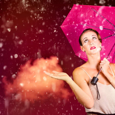downpour: Stylish woman with open palm feeling the downpour of falling rain during the humidity of summer. Retro fashion storm