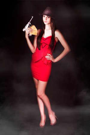 mujer con pistola: Mujer Seductora gángster de pie en sexy vestido rojo con el dinero extorsionado y una pistola en un retrato de un vampiro