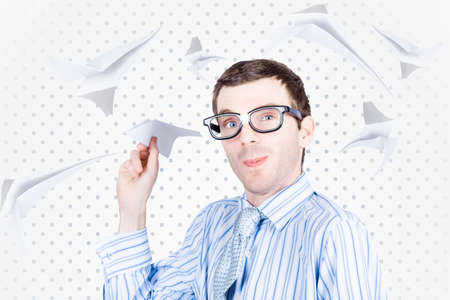 Smart travelling business man throwing paper plane in amongst a flurry of aeroplanes in departure and arrival