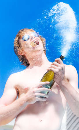 clamped: Shirtless young wealthy hedonistic man with cork clamped between teeth wearing sunglasses spraying champagne into the air from a bottle against blue sky