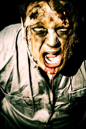 Scary dark horror portrait of an evil zombie screaming out in bloody fear