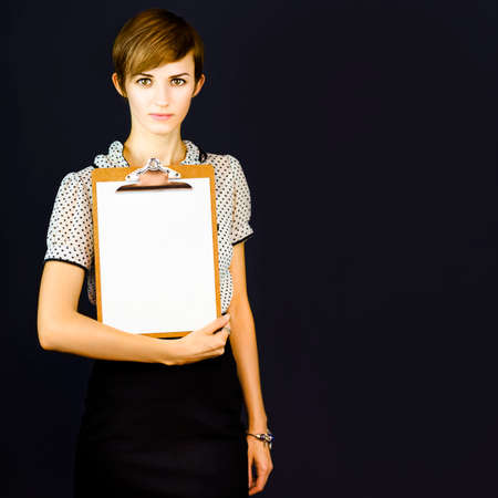 Beautiful young girl on a dark background holding a clipboard with a blank sheet of white paper, conceptual of conducting a survey