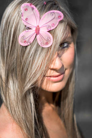 butterfly and women: Beautiful Butterfly Babe Wearing A Fly Hair Tie Trinket On Her Head In The Shape Of A Pink Butterfly Stock Photo