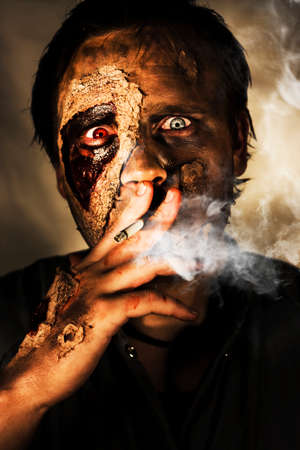 depraved: Dead Sexy Male Zombie Smoking On A Cigarette Cancer Stick With A Look Of Bloodshot Horror, Terror And Fear In A Killing Time Conceptual Stock Photo