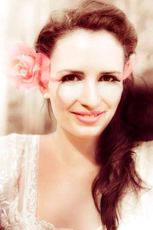 ojos marrones: Soñadora Retrato de la vendimia en la cara de una muchacha bonita que lleva floral postizo, de la pluma de las pestañas mientras que mira en cámara con una sonrisa adorable.