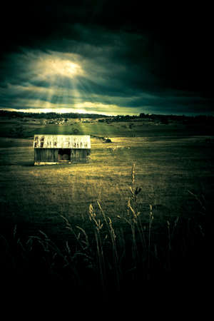 abandoned: Dark Atmospheric Landscape On A Distant Outback Shed In A Farming Field, Being Lit Up By Sun Rays Piecing Clouds, Photograph Taken In Rural Tasmania, Australia Stock Photo