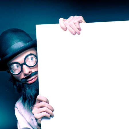 dweeb: Curious Looking Old Nerd Holding Blank Copyspace Billboard On Black Background Stock Photo