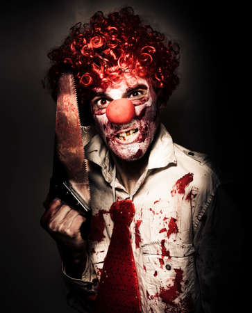 scary man: Frightening Portrait Of A Angry Carnival Clown Carrying Amputation Saw In Dark Slaughter House