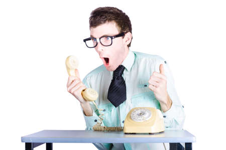 anger management: Portrait of nerdy young businessman shouting into receiver of retro telephone, white background Stock Photo