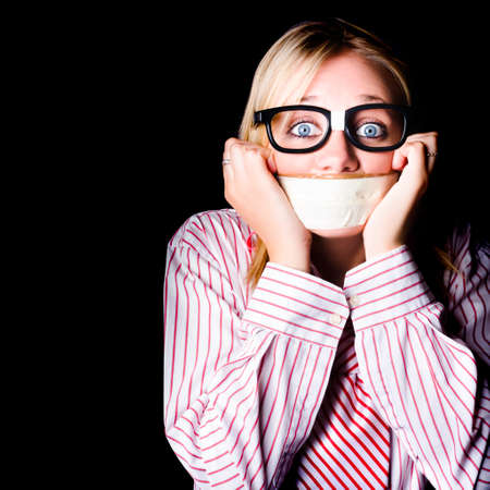 gagged: Young nerdy woman wearing eyeglasses, fearful with tape across her mouth