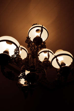 peering: Dark Chandelier Peering From The Shadows Of The Night Stock Photo