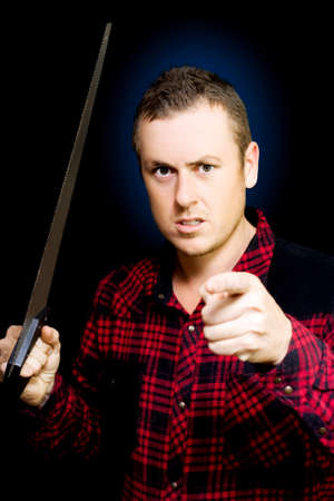 allegation: Angry workman with a wood saw in hand pointing an accusatory finger at the camera as he snarls in frustation, conceptual of anger in the workplace, studio portrait on black