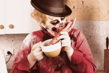 grisly: Snacking zombie gorging on finger food in a dirty kitchen in a depiction of unhealthy eating