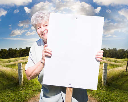 summery: Happy Senior Woman With Blank White Sign In Summery Countryside