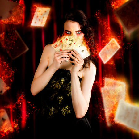 psychic reading: Creative Fine Art Photo Of A Beautiful Mystic Magician Holding Flaming Cards In A Depiction Of Tarot Fortune Telling