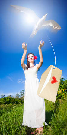 romance sky: A Woman Posting Her Love Letter Into The Deep Blue Sky Of Romance By Carrier Bird Messenger In A Romantic Concept Of Sending A Message Of Love And Romance