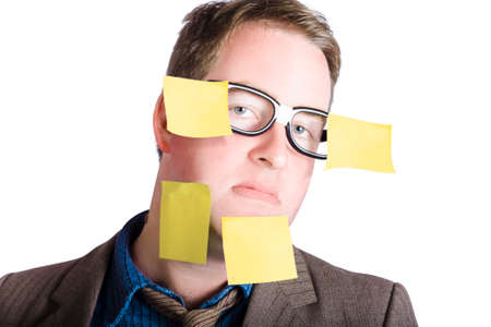 workload: Humorous portrait of an overwhelmed man wearing dorky glasses while carrying his crazy workload on face with yellow sticky notes. Over commitment