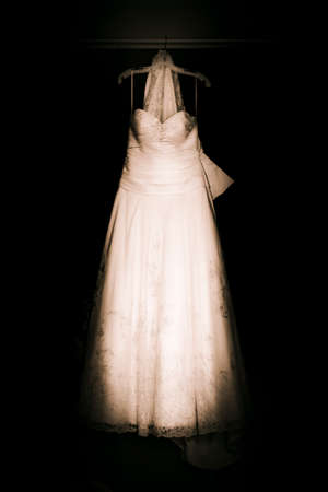 bridal gown: White Vintage Bridal Gown or Wedding Dress Hanging On A Clothes Hanger In A Dark Room