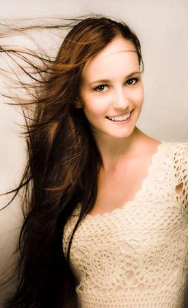 belle brune: Belle naturelle jeune femme souriante avec le vent soufflant à travers ses longs cheveux bruns Banque d'images