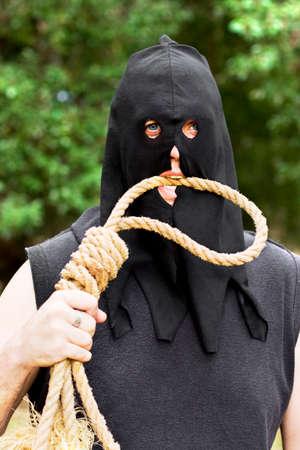 ahorcado: Un encapuchado verdugo Bases para morder al aire libre en una cuerda horca Slipknot como su víctima puede tener mordido más de lo que podía masticar