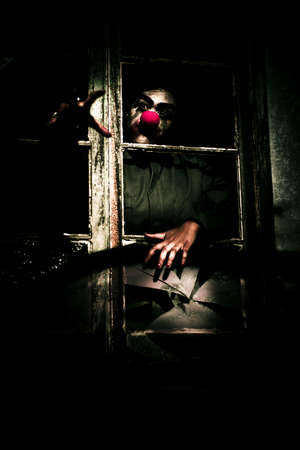 clawing: Spooky Frightening Theme Of A Scary Clown With Red Nose Reaching Out And Clawing Through Window In An Abandoned House