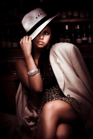 personas sentadas: Elegante estilo y de moda Modelo femenino que desgasta de inclinación sombrero y el abrigo largo de una noche elegante vestido Dentro de una barra oscura en una representación de oscuro Moda Foto de archivo