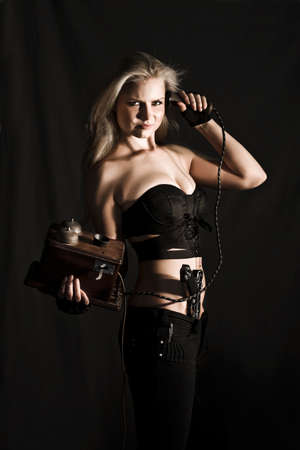 clandestine: Vinatage Female Spy. Sexy blonde toting a handgun in her waistband talking on an old retro telephone handset in shadowy darkness