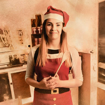 old kitchen: Faded weathered and worn photo illustration of a vintage woman in santa hat standing in old kitchen with baking utensils. Traditional christmas cooking