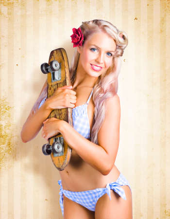 gorgeous girl: Sexy Blonde Aussie Pin-up Girl Holding A Retro Skateboard Shaped Like A Surfboard In A Representation Of The Australian Surf Skate Culture Of The 50s And 60s
