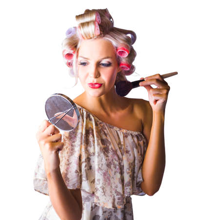 rollers: Attractive young woman with rollers in hair applying makeup in mirror, white background