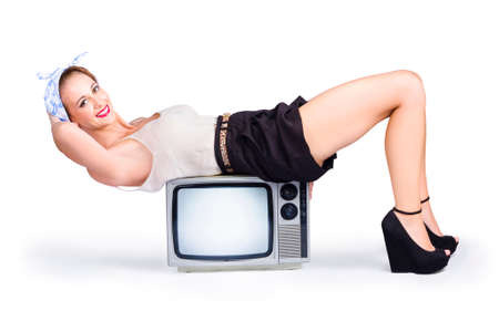 retro housewife: A retro housewife resting on an old-fashioned television set Stock Photo