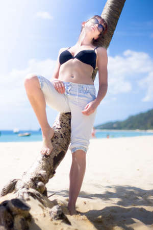 tropicana: An Attractive Young Woman Relaxing On A Shaded Tropical Beach In A Travel Oasis Getaway Stock Photo