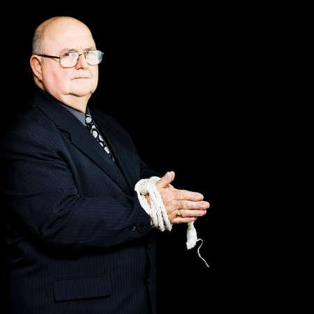 gefesselt: Ein älterer Exekutive steht mit seinen Händen durch ein Seil gebunden um seine eigene Sicherheit suchen gereizt in die Kamera, als er Bruchstelle durch Top-Business-Stress und Übermüdung erreicht
