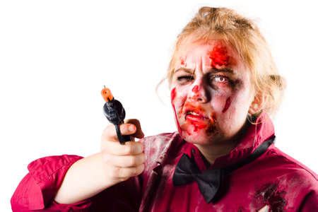 threatening: Sinister and spooky female zombie with face covered in blood looking threatening while pointing revolver on white background