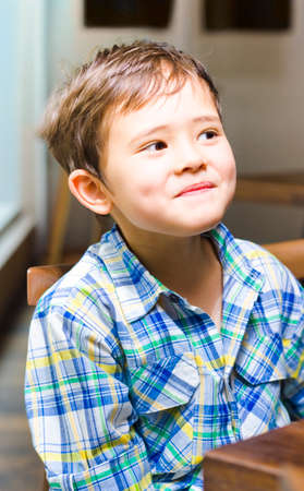 asian preteen: Mischievous young asian boy with a cheeky grin and dimples sitting at a table, close up upper body shot indoors Stock Photo