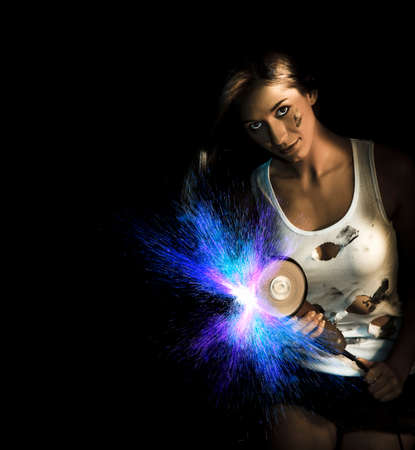 sexy black woman: Creative Dark Photograph Of A Pretty Brunette Using A Heavy Angle Grinder Tool Spraying Blue Sparks While Working In Metal Fabrication At A Steel Industrial Yard