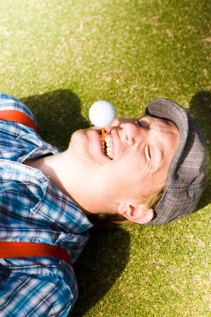 laughing out loud: Insane Sport Nut Crazy About Golf Lying Down On A Golf Course Fairway With A Golf Ball And Tee In His Mouth Laughing Out Loud In A Nutcase Lifestyle Portrait