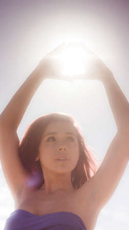 radiant light: Vintage Portrait Of A Young Woman Holding Hands Up Above Head To Catch Rays Of Sun Light Beaming Down From Heavens Above In A Depiction Of Enlightenment