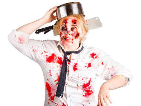 messy kitchen: A zombie undead woman with a metal cooking pan on head. Kitchen nightmares concept Stock Photo