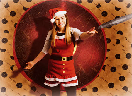 tatty: Beautiful young woman DJ in santa claus costume spinning christmas carols and festive songs at a christmas nightclub disco. Xmas music Stock Photo