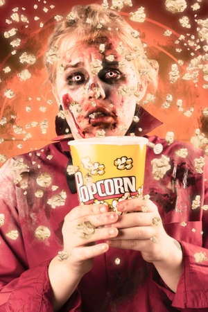 flick: Frightened female ghoul splashing popcorn everywhere at a fright night slasher flick. Scary film concept