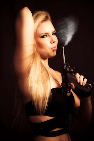 covert: Hot Shot Concept. Gorgeous blonde woman blowing at the wisp of smoking coming from her smoking handgun with a seductive expression Stock Photo