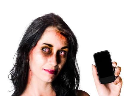 mujer golpeada: Mujer zombie magullado y ensangrentado sosteniendo un teléfono móvil