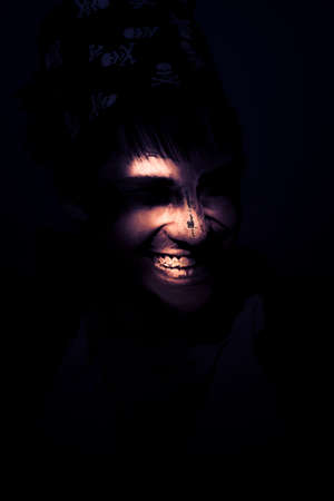sinister: Face Of A Wicked Pirate With Rotting Face Peering Out Of The Moon Light Shadows With A Sinister Smile Or Grin Representing Horror Terror And Madness Stock Photo