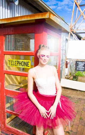 telepathy: Ballerina In Pink Tutu Waits With Eyes Closed Next To A Phone Box In The Sun For A Phone Call In A Communication Conceptual Stock Photo