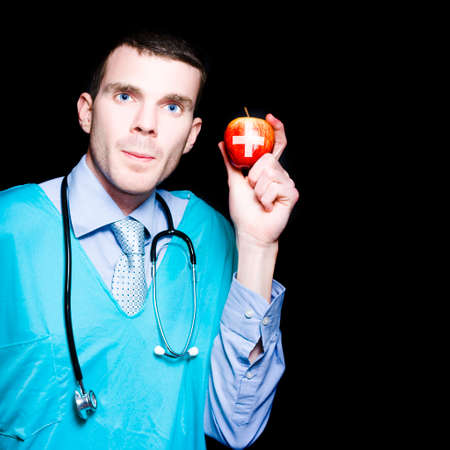 gastroenterologist: Male Gastroenterologist Doctor Holding An Apple With Medical Cross In A Depiction Of An Apple A Day Keeps Constipation Away