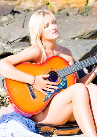 serenade: Person Playing Guitar While On A Beach Vacation Outdoors In A Summer Serenade Concept Stock Photo