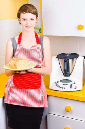 pert: Cute baking woman holding fresh bread with bread making appliance in yellow kitchen